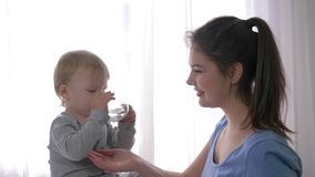First child successes, happy kid boy independently drinks mineral water from glass beside to young smiling mother in stock video