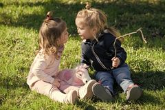 First childish love. Brother and sister kiss on sunny day. Boy and girl sit on green grass. Family, love, trust. Kids play with stick and toy horse. Children Royalty Free Stock Photography