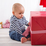 First Christmas: baby unwrapping a red present with a red checke Stock Images