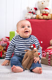 First Christmas: barefoot baby with moose amongst presents and c Royalty Free Stock Photos