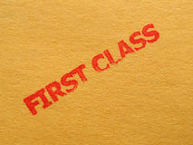 First class. Red ink stamp over brown cardboard Royalty Free Stock Images