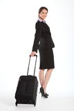 First class business travel beautiful Asian woman. Full body shot of beautiful young Asian business woman, with happy smile, walking with a black suitcase. Woman Royalty Free Stock Photography
