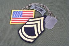 First Class för USA-ARMÉsergeant frodig lapp, prickskyttflik, flaggalapp och hundetikett på unifo för olivgrön gräsplan Arkivfoton