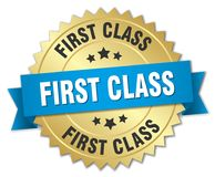 First class. Gold badge with blue ribbon Stock Image