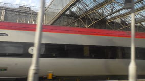 First class train car or carriage. First class cars or carriages of red silver train standing at the station.View from moving train window stock video footage