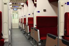First class train with red velvet cushion luxury,perspective interior view of a modern high speed train. Red chairs with convenient for tourist and travel on royalty free stock image