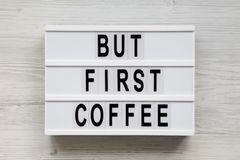 `But first coffee` words on modern board over white wooden background, top view. Overhead, flat lay, from above. `But first coffee` words on modern board over stock photos