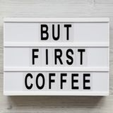 `But first coffee` words on modern board over white wooden surface, top view. Overhead, flat lay, from above.  stock photo