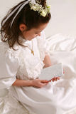 First communion 3. Smiling little brunette girl making first communion Royalty Free Stock Photos