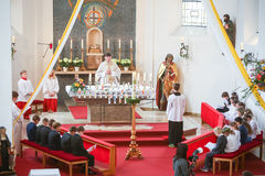 First communion. NANDLSTADT, GERMANY - MAY 7, 2017 : The priest holding the mass at the first communion with young boys and girls sitting in front in Nandlstadt Stock Images