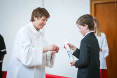 First communion. NANDLSTADT, GERMANY - MAY 7, 2017 : The priests assistant helping a boy to light up the candle in church at the first communion in Nandlstadt Stock Photography
