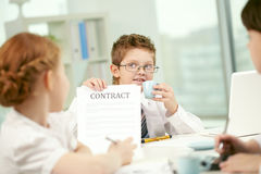 First contract. Little businessman showing contract to his colleagues stock photo