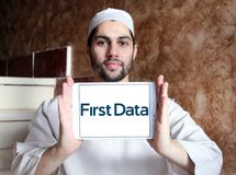 First Data Corporation logo. Logo of First Data Corporation on samsung tablet holded by arab muslim man. First Data is a global leader in commerce enabling Stock Photo