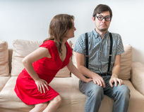 First date of a couple. Young woman is flirting with shy man sitting on sofa royalty free stock photos