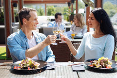 Nice positive man and woman having a date. First date. Nice positive delighted men and women smiling and drinking wine while having their first date Royalty Free Stock Image
