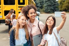 First Day. Classmates going to school by bus girls standing close-up hugging taking selfie on phone