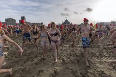 First day of the new year dive 2018. SCHEVENINGEN, 1 January 2018 - Dutch people following the strong tradition of the first new year dive run toward the frozen stock photos