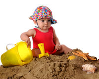 First Day in the Sand. An adorable baby girl in a bathing suit and sun-hat playing in the sand. Isolated on white stock images
