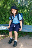 First day of school. Shy little girl looking a bit nervous for her first day of school; dressed in full blue uniform and sitting on a bench Royalty Free Stock Photography