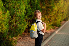 First day at school. Elementary Student, Little Boys, Backpack. Little schoolboy comes back from school in good mood. The boy goes on a footpath. He has raised Stock Image