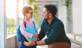 First day at school. father leads  little child school girl in first grade. First day at school. father leads a little child school girl in first grade stock photo