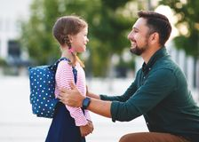 First day at school. father leads little child school girl in f Stock Images