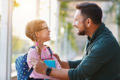 First day at school. father leads little child school girl in f Royalty Free Stock Image
