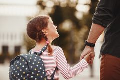 First day at school. father leads  little child school girl in first grade. First day at school. father leads a little child school girl in first grade royalty free stock image