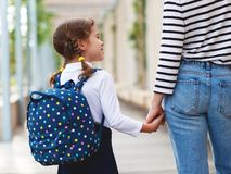 First day at school. mother leads little child school girl in f