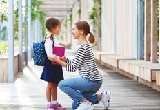 First day at school. mother leads little child school girl in f royalty free stock photography