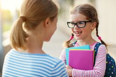 First day at school. mother leads little child school girl in f. First day at school. mother leads a little child school girl in first grade stock image
