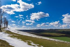 First day of spring landscape. Snow trees blue sky and puffy clouds stock image