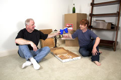 First Dinner in New Home. Man and woman eating pizza dinner on the floor amongst moving boxes in their new home Stock Image