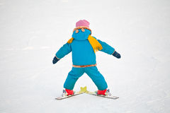 The first downhill. Little child doing his first downhill on alpine skis, standing back closeup on snow background stock photography