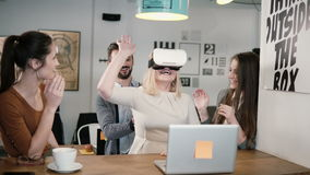 First experience with virtual reality glasses young team supports young beautiful blond girl in modern startup office Royalty Free Stock Photo