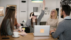 First experience with virtual reality glasses young team supports young beautiful brunette girl in modern startup office Stock Photography