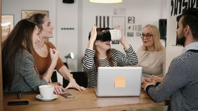 First experience with virtual reality glasses young team supports young beautiful brunette girl in modern startup office Royalty Free Stock Image