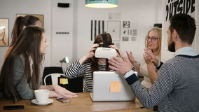 First experience with virtual reality glasses young team supports young beautiful brunette girl in modern startup office Royalty Free Stock Photos