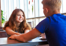 First feelings. Teenage couple meeting in modern cafe Royalty Free Stock Images