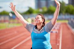 First on finish. Successful over-size woman raising hands after crossing finish Royalty Free Stock Photography