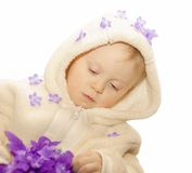 First flowers. Little girl with lilac silk flowers on white background, space for text Royalty Free Stock Photo