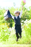 First-form schoolboy with flowers and satchel Royalty Free Stock Photos