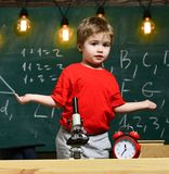 First former confused with studying, learning, education. Child with confused expression near microscope. Primary school Stock Photos