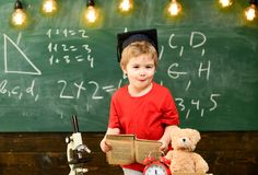 First former interested in studying, education. Kid boy in graduate cap holds book in classroom, chalkboard on royalty free stock images