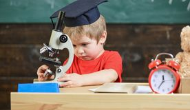 First former interested in studying, learning, education. Kid boy in academic cap work with microscope in classroom. Chalkboard on background. Child on busy Royalty Free Stock Images