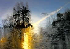 First frost. Late autumn. Frosty golden sunrise reflected on lake surface. Part of the lake was covered with a thin layer of ice. Falling leaves create ripples Royalty Free Stock Image