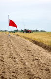 The first furrow in the field after harvest. The red flag was erected on the site of the first furrow on the field after harvesting grain crops Royalty Free Stock Photography