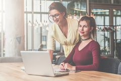 First girl is standing near table,second is sitting next to her.Teamwork.Girls blogging,working,learning online. Royalty Free Stock Photos