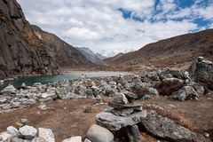First Gokyo lake and stone pyramids. The smallest of Gokyo lakes in Nepal Himalayas and surrounding scenery, including traditional towers of stones stock images