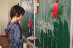 First grade child, learning math, shapes and colors at school. Standing in front of blackboard stock photo